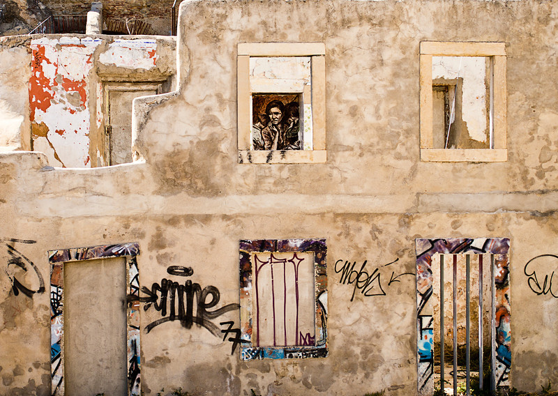 A wall of a ruined building near the Castelo in Lisbon has been defaced with various graffiti drawings. The windows frame additional drawings inside including a derivative portion from Migrant Mother.