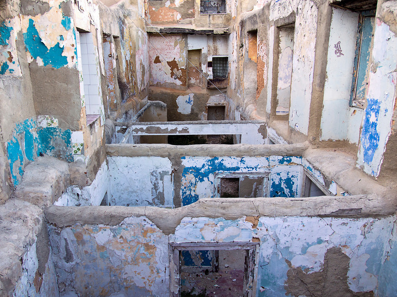 The interior of an apartment building in Lisbon that is open to weather from the top and through open windows. Peeiling paint, cracked concrete and missing floors illustrate urban decay.