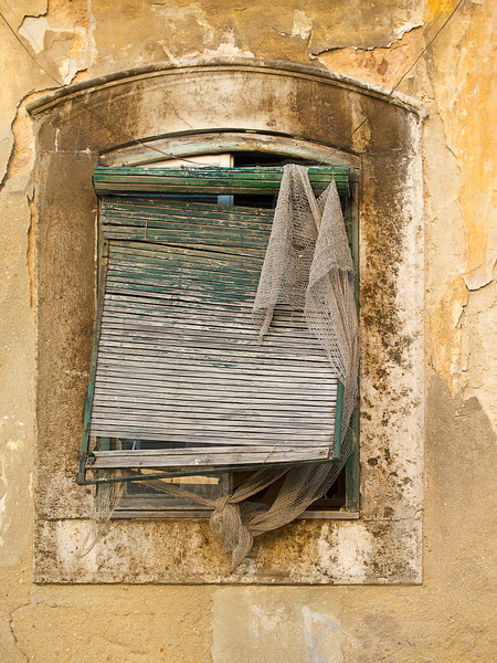 A window on a building wall inthe Castelo barrio of Lisbon shows an old faded, weathered set of blinds and fragments of a curtain.