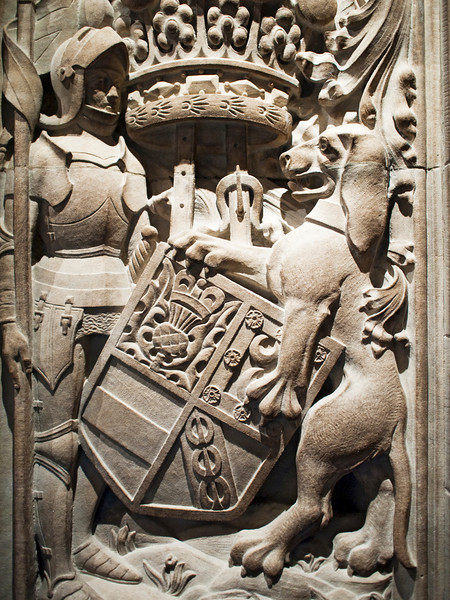 A knight and lion holding a family crest as observed on the entrance column to the Thistle Chapel in St. Giles Cathedral in Edinburgh, Scotland.