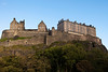 Edinburgh Castle rises above the city protected by natural cliffs and high rock walls. The guards' stone barracks and other buildings are all part of the landmark structure.