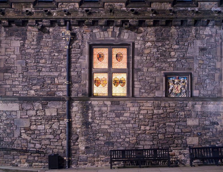 The exterior wall of the Great Hall of Edinburgh Castle at night. The stained glass windows with the emblems of past kings of Scotland are glowing in the dark next to the symbol of royalty.