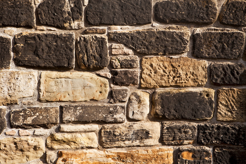 A stone wall in Edinburgh Castle shows a pattern from unevenly sized light and dark stones and mortar.