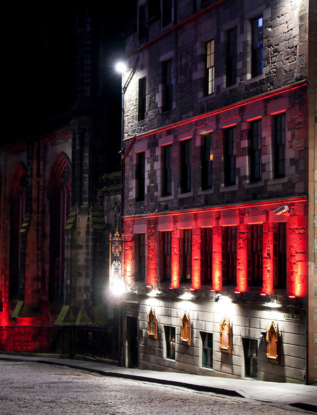 A building on the Royal Mile in Edinburgh's Old Town is illuminated with white and red lights at night.