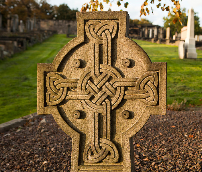 A grave marker with a traditional entwined pattern carved into the stone. Isolated against a white background.