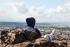 A woman sitting on top of Arthur's Seat is looking at the view over Edinburgh.