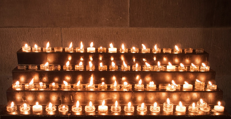 A candle stand full of small votive candles lit for prayers at St. Giles Cathedral in Edinburgh.