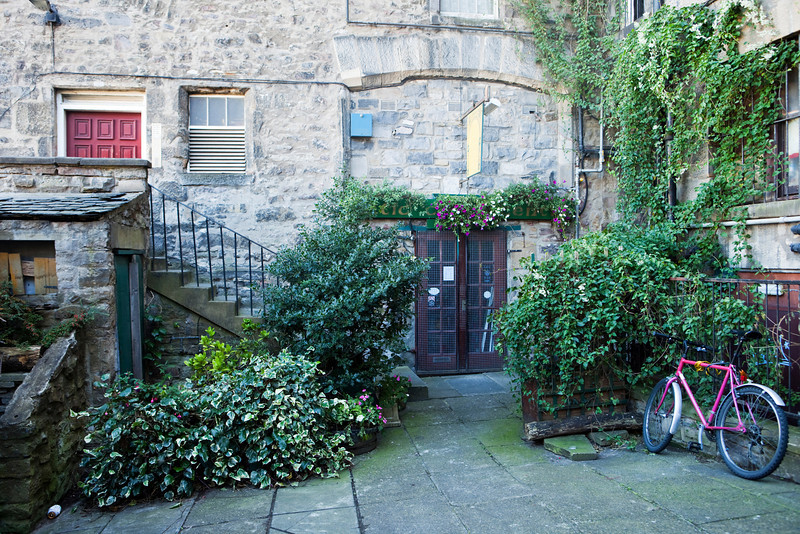 A small close, or narrow alley, in Edinburgh with a garden in the courtyard.