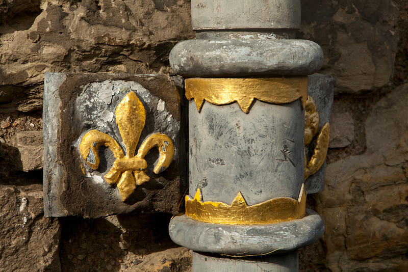 A detail from an old lead drain pipe at Edinburgh Castle. The gold paint on the fleur de lis detail and pipe fittings provide a bit of brightness to the dull grey lead pipe.