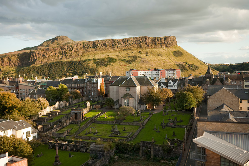 A view of Edinburgh from Calton Hill looking towards the Salisbury Crags in Holyrood Park. At the bottom is one of Edinburgh's ancient graveyards located next to Canongate Kirk.