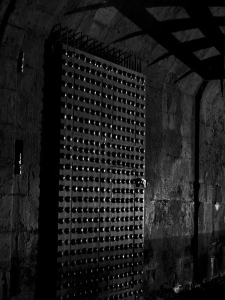 The inside castle gate to Edinburgh Castle at night shows a little bit of light reflecting off the metal studs in the door and shadows from the portcullis. In black and white.