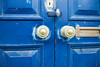 A blue door with bronze doorknobs, mailslot, and keyhole. The scuffed and faded paint together with the slightly askew door panels has a grungy feel to it.