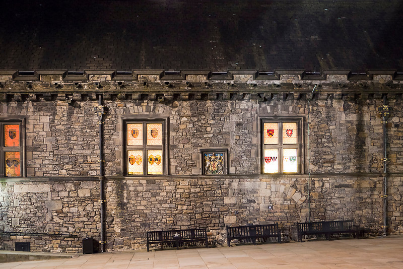 The windows of the Great Hall of Edinburgh Castle glow at night from across the courtyard.