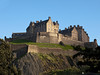 A view of Edinburgh Castle from below showing the rocky cliffs, ramparts and other defenses from attack.