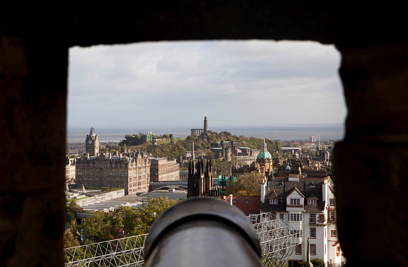A view of Edinburgh framed through one of the rough stone gunports of Edinburgh Castle. The Old City is in the foreground and parts of the New City and Calton Hill are in the background.