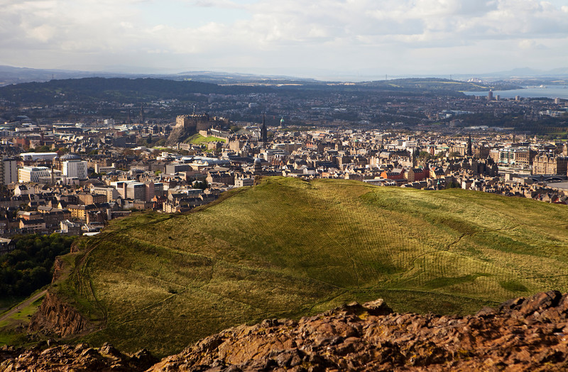View of Edinburgh central city, including Edinburgh Castle, from Arthur's Seat which is an extinct volcano in Holyrood Park. This part of the park is bounded by the Salisbury Crags.