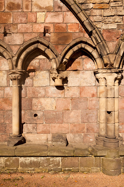 The exterior wall of the Holyrood Abbey is constructed with a series of stones filling smaller gothic arches. This one segment of the ruins shows a missing pillar with the repeated arch motif.