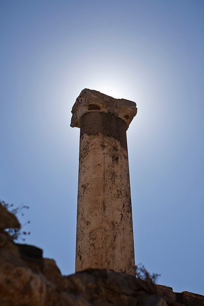 A single pillar put up by Greeks or Romans is backlit by the sun. It stands alone at the ancient city of Ephesus, near Izmir in Turkey.