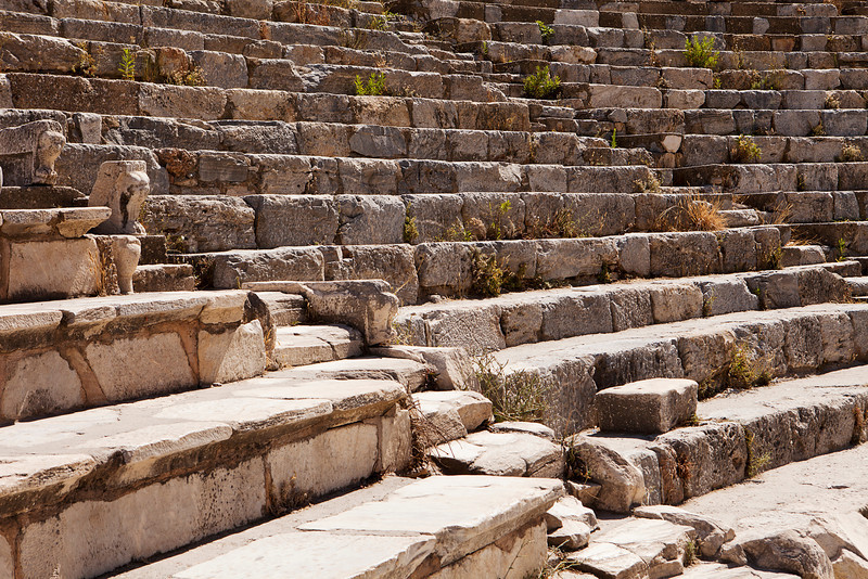 A section of seats in the old Roman theater at Ephesus near Izmir in Turkey. There are two aisles leading up through the tiers of stone seats.