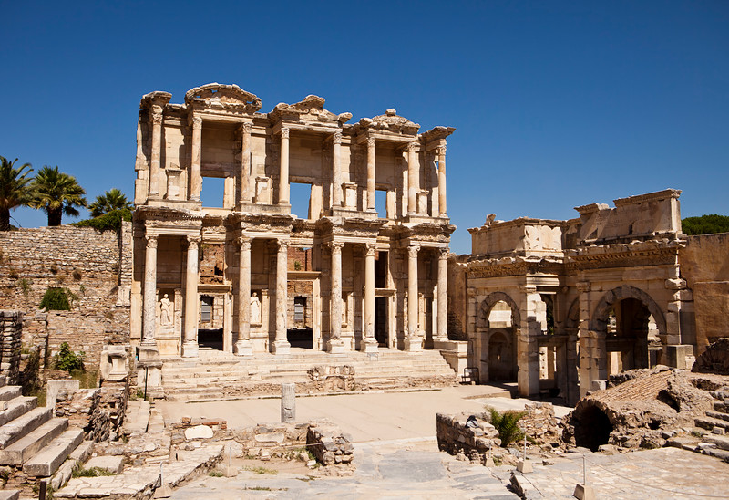 The front facade and courtyard of the library building at Ephesus is an imposing ancient Greek and Roman structure. Built from old stone and reconstructed by archaeologists, it is a popular tourist stop near the city of Izmir in Turkey.