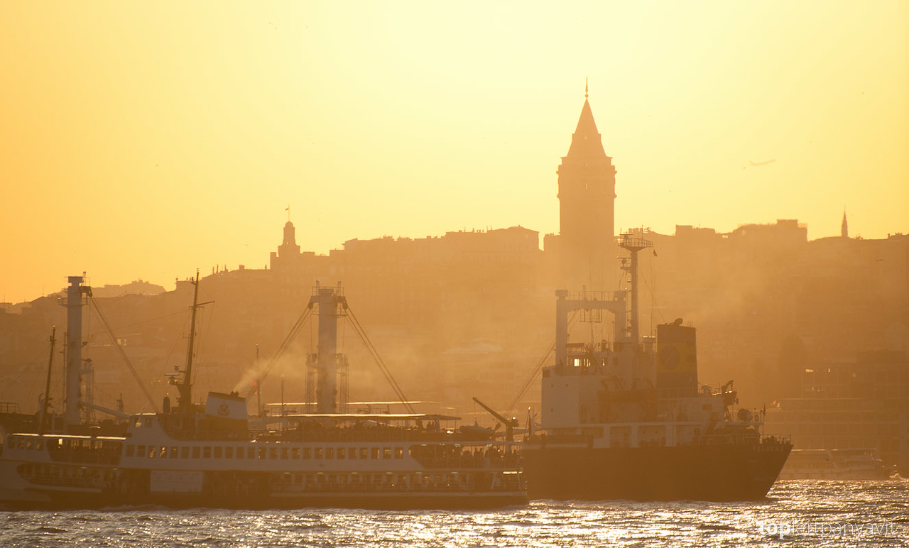 Ferries and ships sail the Golden Horn in the foreground with the silhoutte of the Galata Tower at sunset