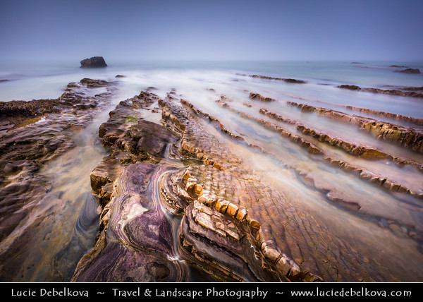 Europe - UK - England - Cornwall - Bude - Porthbud - Charming small seaside resort town along stretch of stunning coastline located on north Cornish coast - Eroded vertical rock folds of Bude Formation exposed on sandry beach