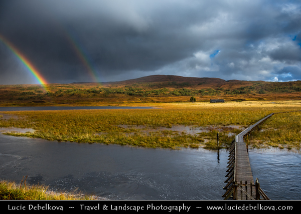 Europe - UK - United Kingdom - Scotland - Western Scottish Highlands - Landscape around Loch Gowan - Freshwater loch in Wester Ross - Dramatic changeable weather with rainbow - Footbridge over the lake