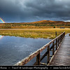 Europe - UK - United Kingdom - Scotland - Western Scottish Highlands - Landscape around Loch Gowan - Freshwater loch in Wester Ross - Dramatic changeable weather - Wooden footbridge over the lake with Rainbow