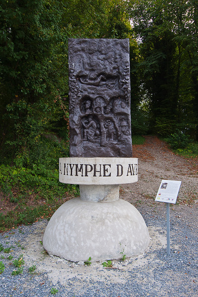 "This was the site of Aveluy, a village that as the interpretive plaque reads was ""completely ravaged during the various offensives."" (The French wikipedia page says ""destroyed."")<br /> <br /> But this statue memorializes a piece of vernacular art created by the the soldiers in the side of a trench depicting things they missed, notably the recumbent nude young lady at top who has become known as the Nymphe d""Aveluy.<br /> <br /> This trench section was photographed and made into postcards and has recently been recreated at what is now called Crucifix Corner (see previous photo)."