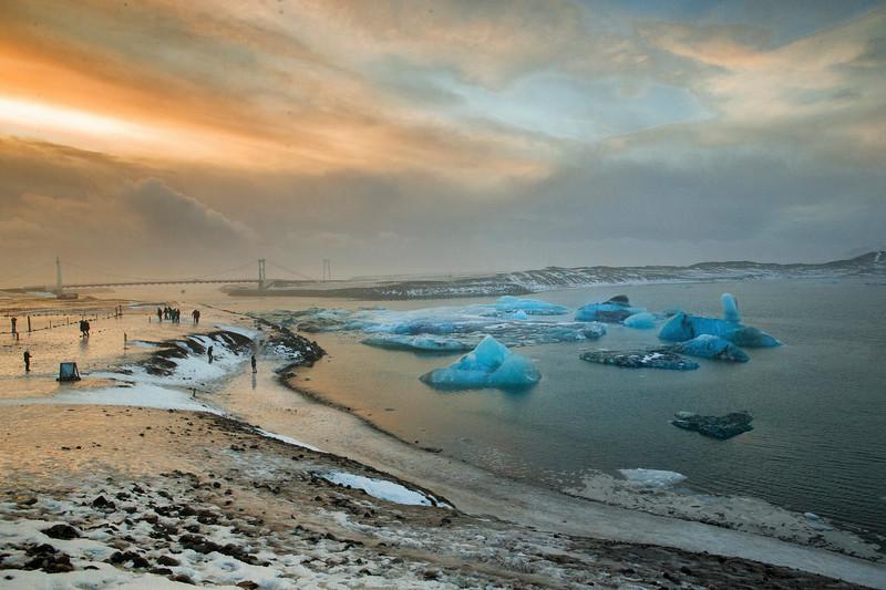 Tourists gather at Jokulsarlon during sunrise in Southern Iceland