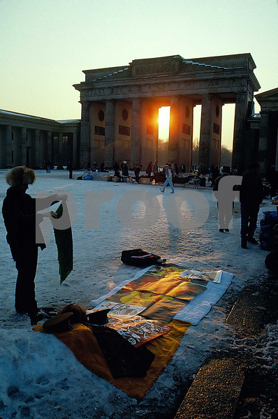 Soviet Union and East Germany military clothing and equipment for sale and spread on blankets in the snow by the Brandenburg Gate in Berlin, Germany after the wall came down.