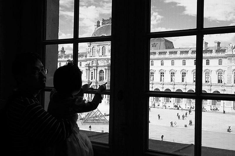 A father and daughter admire the view inside the Louvre.
