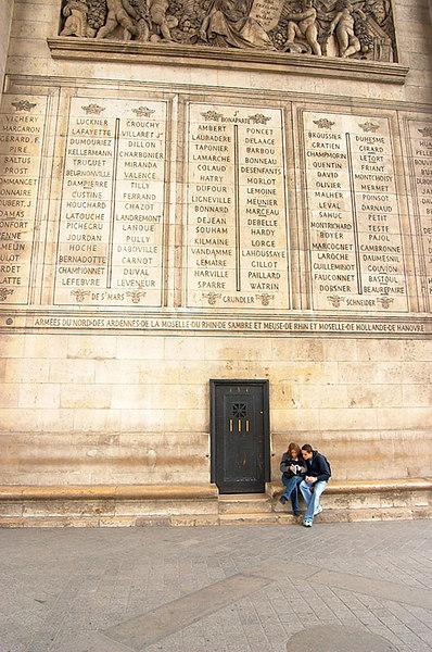 Two tourists decide where to go next at the Arc de Triomphe.