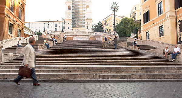 A businessman, in a hurry, walks by the Spanish Steps.