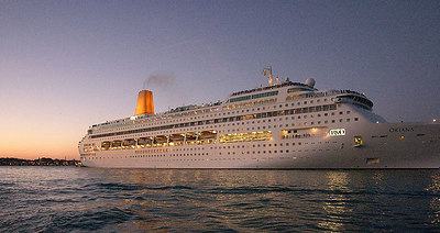 A cruise ship leaves Venice at dawn.