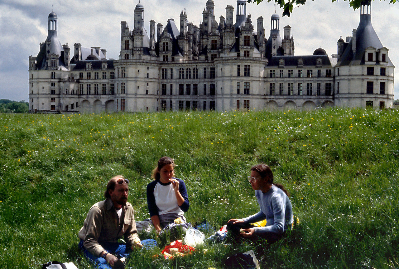 Picnic - Chateau Chambord<br /> <br /> Day 39 - May 19 - Chateau Chambord - 11 miles - I had seen the postcards, but was still unprepared for the majesty and magnificence of Chateau Chambord. It is a fairy tale - a stone wedding cake - iced with a riot of spires, towers and gables. <br /> <br /> The Chateau was closed for lunch. (And, like the dog in our first French restaurant which was a harbinger of all the dogs that followed, our arrival at our first Chateau during the lunch closing, seemed to set a pattern we would repeat time and again.) While we waited for the next tour, we spread out our picnic on the front lawn and marveled at the elaborate structure before us while sipping some excellent cider beers.