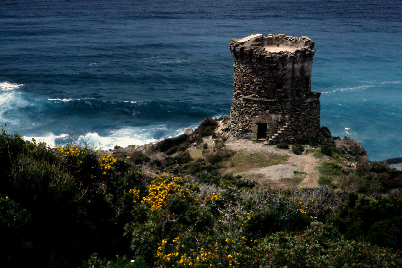 Corsican Tower<br /> <br /> Day 21 - May 1 - When the road is high above the surf we look down on black sand beaches, white rocks, green rocks, the curious round stone towers with crenellated tops looking for all the world like rooks escaped from an oversize chess set, and the shiny domes of the monasteries, all breathtaking in the Mediterranean sunlight. When the road descends to the shore in a white knuckle rush, we see the waves are a little taller today, maybe 2 or 3 feet, pushed up by an off shore breeze. We stopped often today to explore the beaches, to admire the views, to photograph the flowers, and to just breathe, an exotic experience by itself on this garden island.