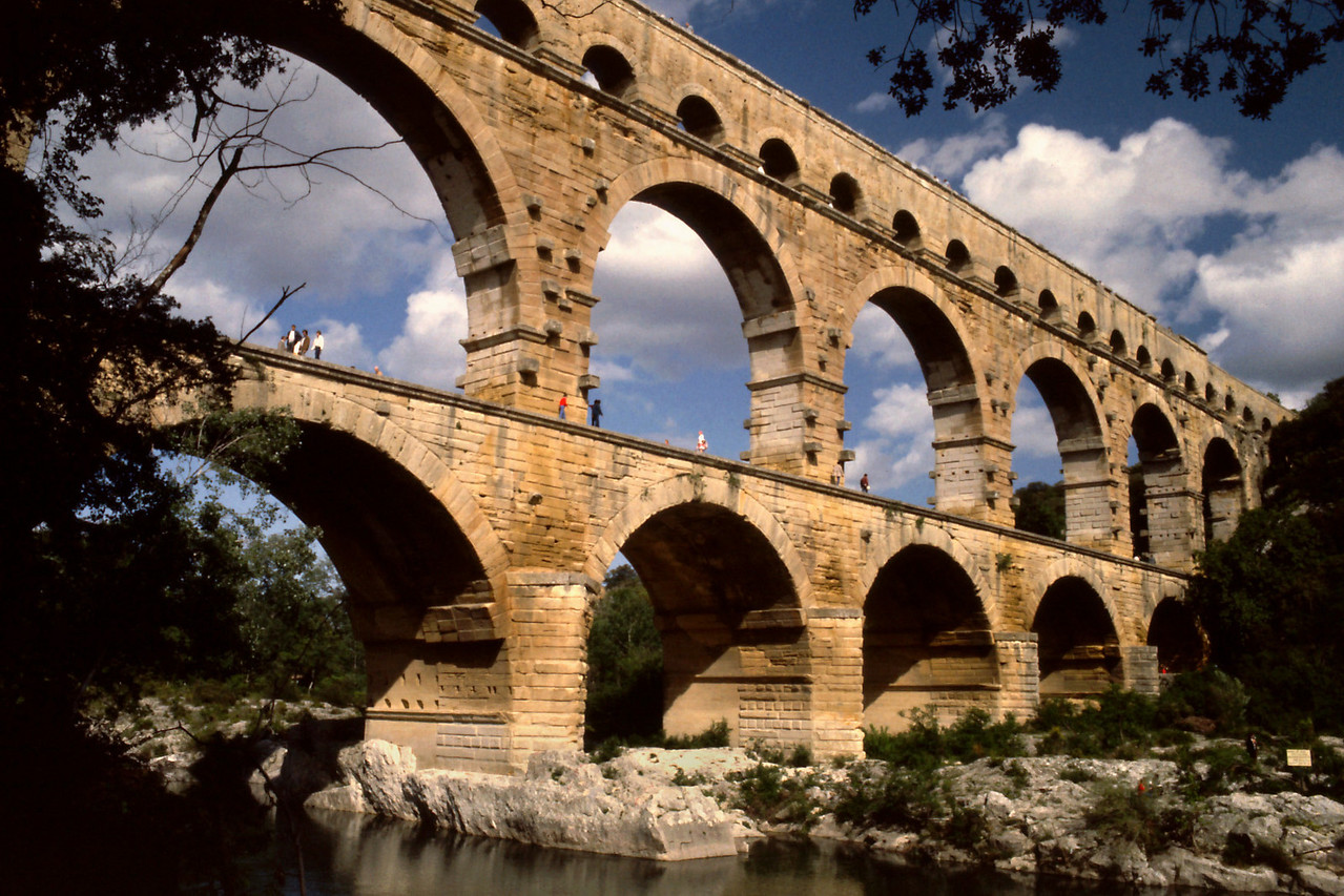 Pont du Gard3<br /> <br /> Day 28 - May 8 - In the late afternoon we arrived at a major attraction. A crowd of tourists were assembled to view the Pont du Gard. It is a magnificent Roman aqueduct, three tiers of graceful stone arches over the clear, green waters of the Gard. Awesome in size and graceful in form, it is a treat for the eyes and a wonder for the mind.