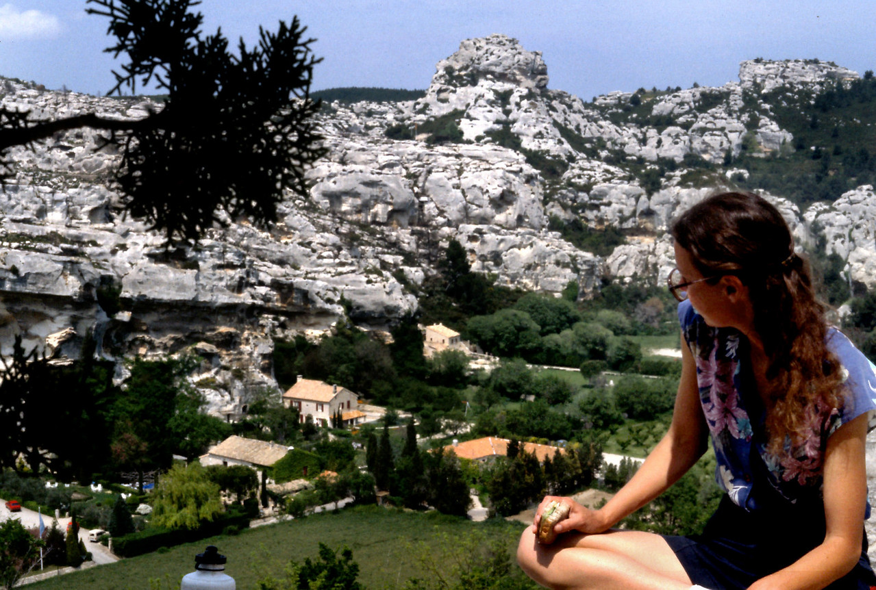 Les Baux, Rita<br /> <br /> Day 26 - May 6 - Les Baux - Continuing north, parallel cliffs of white limestone appeared on either side of the road. Had the rocks been redder, I might have thought I was in Utah. The road climbed up to the top of a hill where we found the fantastic little town of Les Baux. The streets were narrower, steeper, and crookeder than any we had yet seen, walled by adorable little shops, most selling expensive trinkets for wealthy tourists - jewelry, olive oil, dolls in traditional costumes, pottery, wine and herbs. <br /> <br /> Rita struck up a conversation with one jeweler who had been to Taos, and he gave her a sterling silver ring. <br /> <br /> Flowers were the local specialty, and they were available dried in jars, cast into plastic, bundled into sachets, and as oils, extractions and perfumes. <br /> <br /> We made our simple picnic lunch on a sunny stone wall with a view out over the surrounding cliffs, hills and canyons of white stone. The limestone is heavily pocked with little one-room caves and, with binoculars, I could see the local inhabitants had improved some of these caves with walls of stacked stone. Some caves were completely walled in and had doors and windows, others were partially open for me to view the contents stored there: jars, wine bottles, boxes, an occasional old car, or workbench; not that different from the objects visible in the open garages of suburban America, but somehow made much more interesting in the context of French cliff caves.