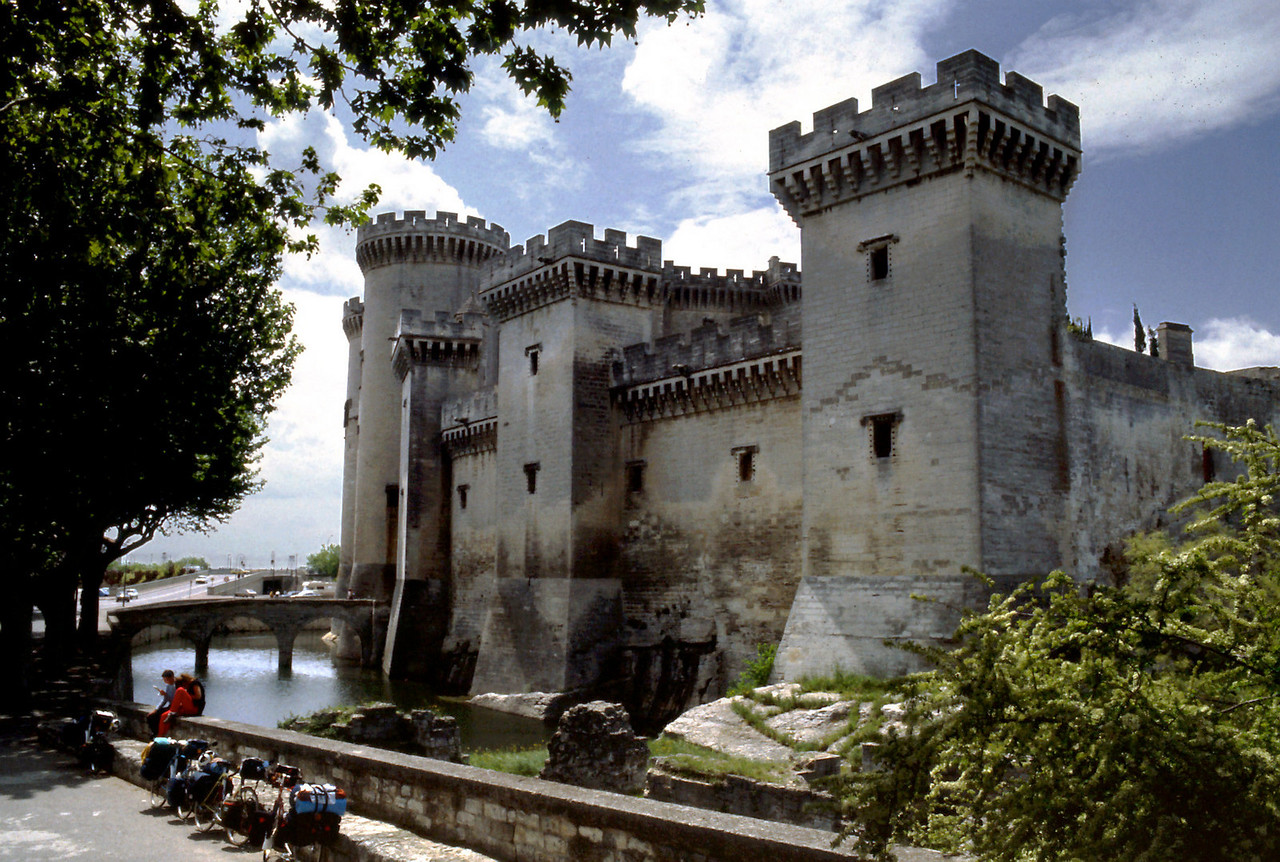 Castle, Tarascon<br /> <br /> Day 28 - May 8 - 27 miles - It rained off and on all night, but a little sun is shining this morning. After showers and breakfast, we managed to cycle 3 blocks before we were ambushed by some strawberry tarts, a swan of a cream puff, and a bun filled with something rich. Route D15 north from Arles took us through flat farmland - big boring fields & head winds. <br /> <br /> At Tarascon we stopped to eat lunch on the wall of a castle moat. The castle tour included a grand spiraling stone staircase for a view of the town from the tower. This castle is still in good enough condition to imagine someone living in it.