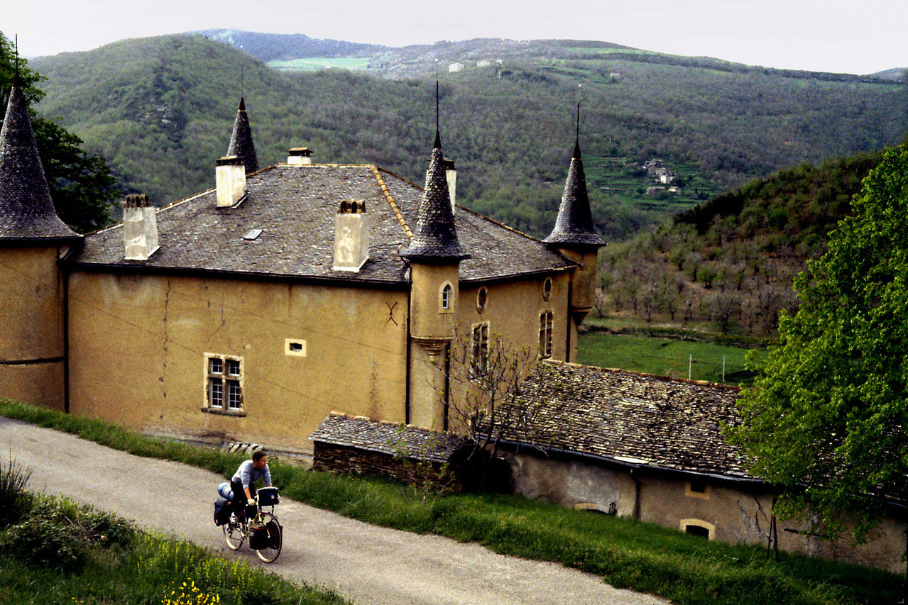 Cevennes Mountains, Rita<br /> <br /> Day 30 - May 10 - 23 miles - Got up late under gray skies, then made eggs , zucchini, cheese, bread, jam, and tea. Stopped at Anduze for groceries before heading up the River Gard. We are entering the Cèvenne Mountains, but hope to avoid a lot of climbing by sticking to the rivers. This is the area Robert Louis Stevenson wrote of in Travels With a Donkey. <br /> Several good views down on the pretty green waters of the Gard. <br /> <br /> At St. Jean du Gard we turned north (D983) and climbed a steep ridge, then followed a pretty little tributary stream of the upper Gard (Gardon de Mialet) as it ziged and zaged around sharp ridges of stone jutting down from the mountains surrounding us. Goats and sheep make pretty white dots on the steep green pastures near the few small hamlets, little stone towns with postage stamp gardens, but mostly the scenery is of the natural river gorge.