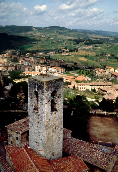 San Gimignano Tower2<br /> <br /> In the niches of the stone towers clusters of yellow flowers nod in the warm Tuscan breeze. Pigeons court and coo.