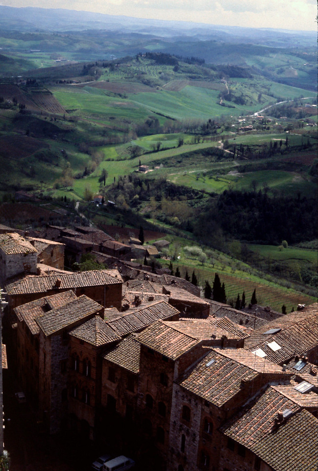 San Gimignano View<br /> <br /> Day 11 - April 21 - On spiraling stone steps worn hollow by the feet of seventeen centuries, we climbed to the top of one of the bell towers. At the top of the tower a roof of timber and tile shelters the massive bells above our heads. <br /> <br /> At our feet are the red tiled roofs of San Gimignano, and beyond the edge of town, the Tuscan countryside is spread out like a crazy quilt. The high, rounded hills are covered by a patchwork of silvery olive groves, brown plowed fields, and the bright green of new leaves on the grapevines. <br /> <br /> Rows of tall skinny Cyprus trees line up like rows of toy soldiers. Drifting up from the landscape below we hear the tinkle of sheep bells, the cackle of ravens, and the haunting murmur of a distant cuckoo.