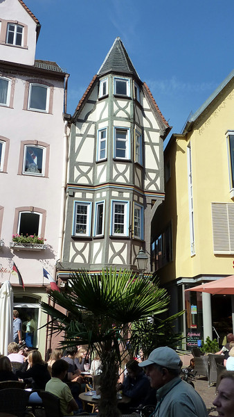 A narrow house, widening with each floor above.