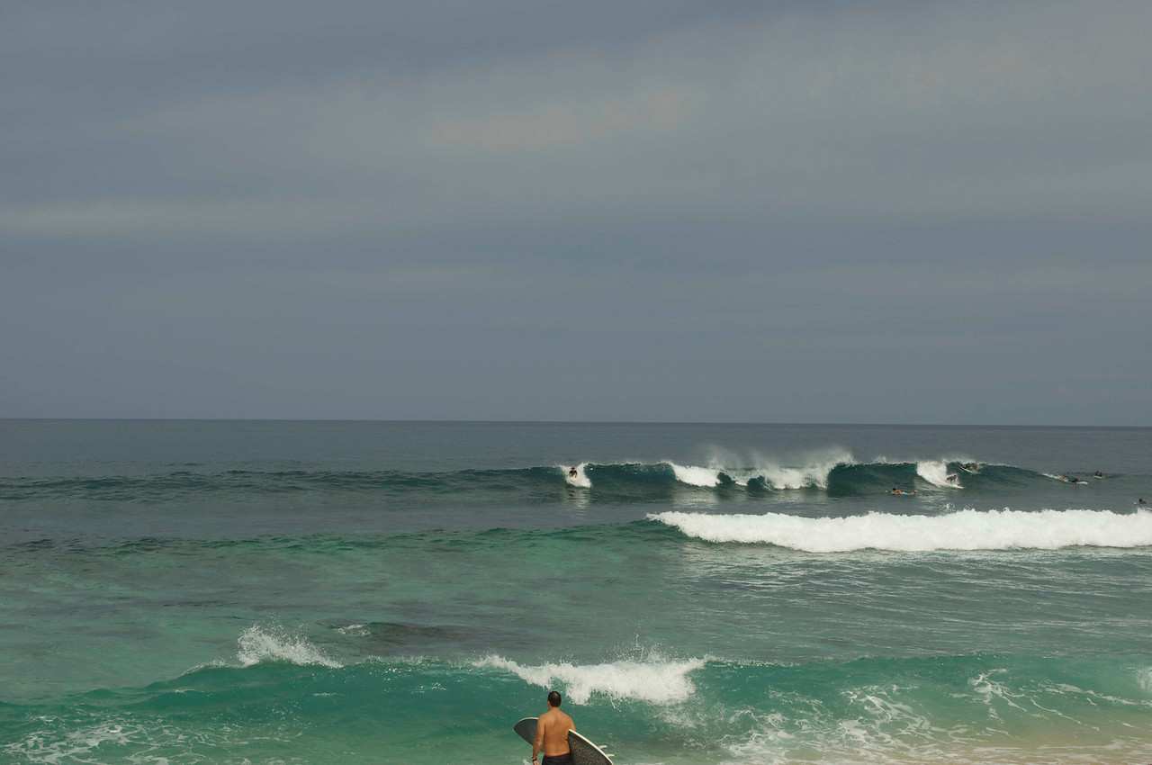 Over a half-dozen surfers are visible in this photo during a normal surf day.