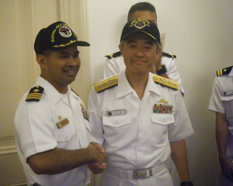 The Mustin's captain exchanges ballcaps with the superintendent of the Maritime Officer Candidate School.