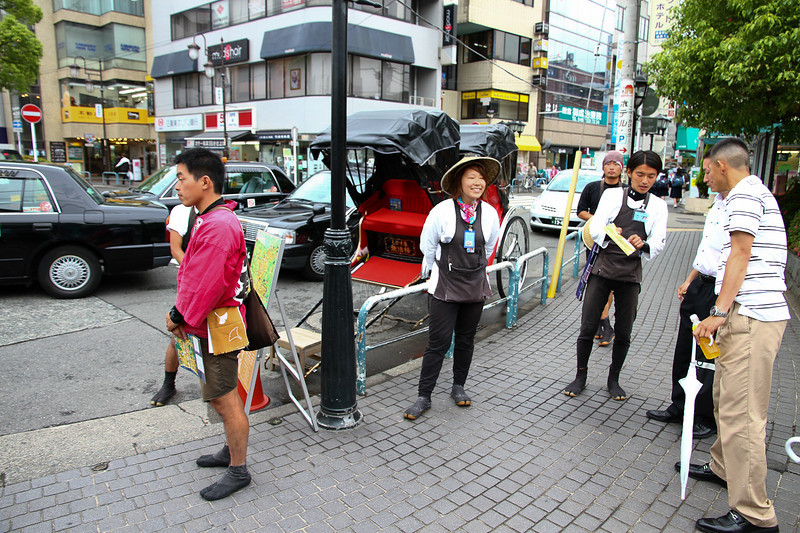 """Human powered taxis"" in Kamakura.  The little carts are pulled by people!  In the background, black motorized taxis wait for customers at the train station."