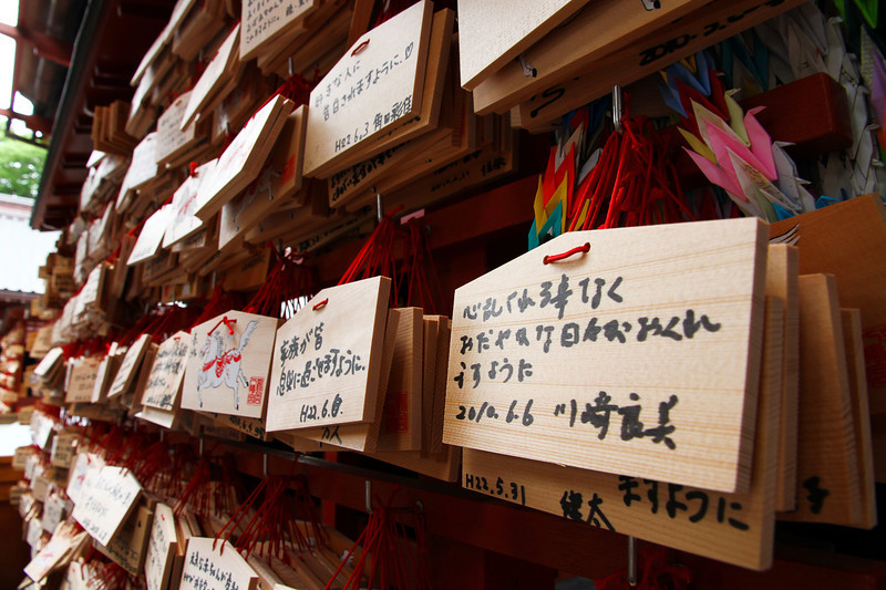 At this Shinto temple, intentions are written on wooden cards and hung in front of the shrine.