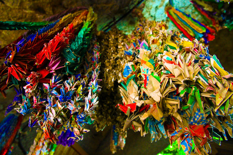 Origami cranes hang from the ceiling in a Japanese shrine.