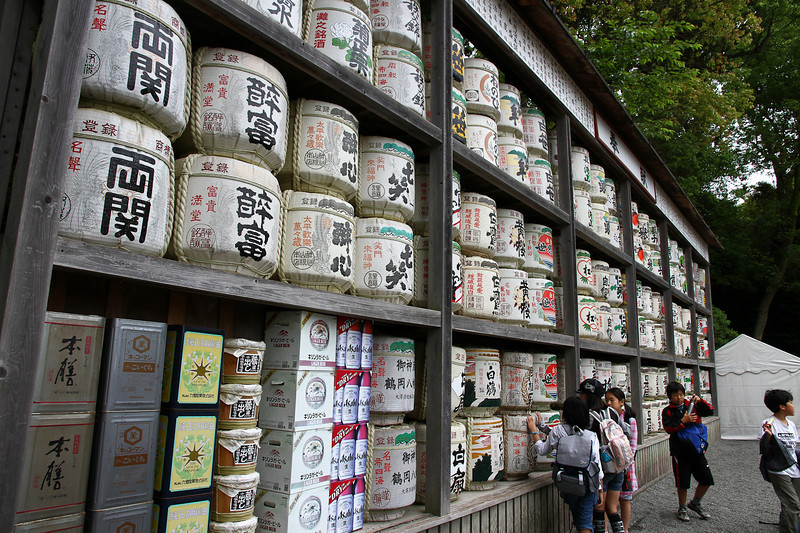 Little kids admire barrels of sake at a Japanese temple in Kamakura.